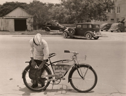 """A """"drugstore cowboy"""" preparing to deliver orders on his bicycle in Texas, 1938 Photograph by Luis Marden, National Geographic"""